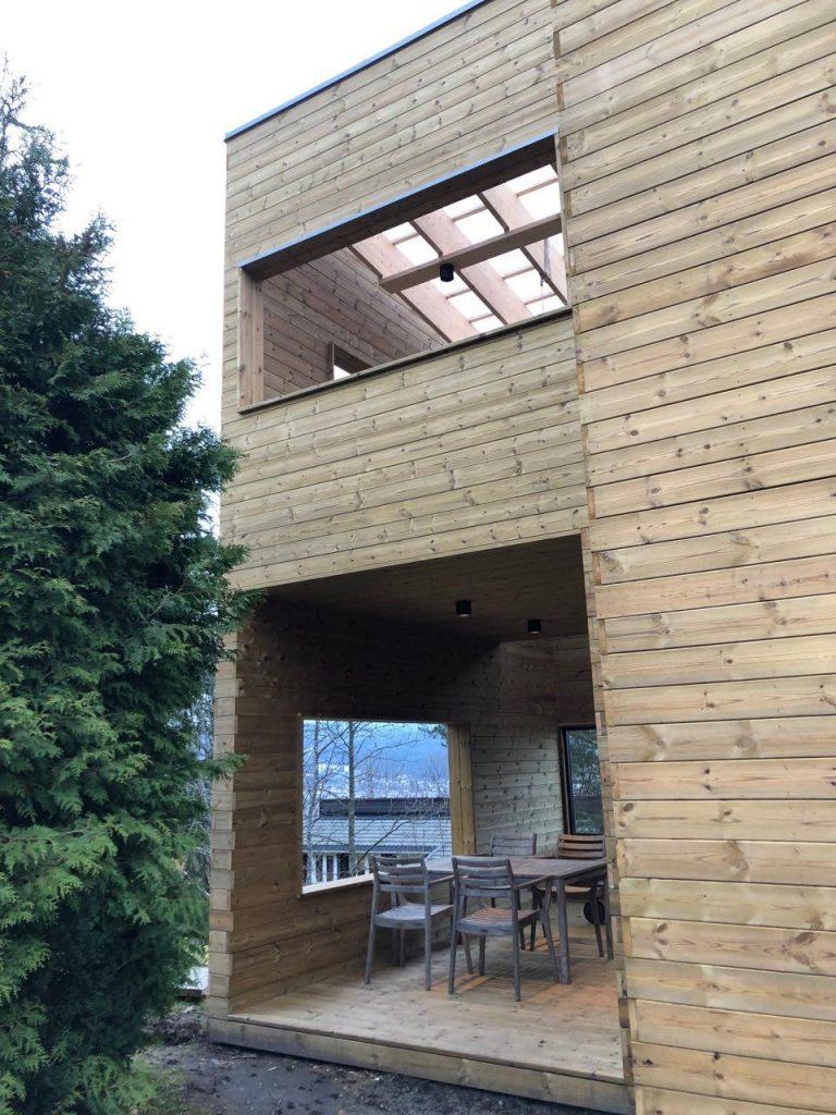 Overbygd terrasse og balkong, stilrent og tilrettelagt som en integrert del av boligen.